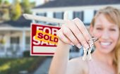 Excited Woman Holding House Keys and Sold For Sale Real Estate Sign in Front of Nice New Home. poster