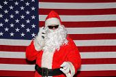 Santa Claus stands in front of the American Flag.  Santa Claus Smiles and Poses in front of an Ameri poster