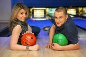Man and woman lie on parquet leaning against an elbow and everybody holds ball for bowling, focus on