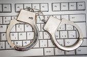 Top View Of Keyboard And Handcuffs - Cyber Crime Concept poster