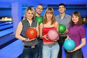 Three girls and two men stand alongside and everybody holds  ball for bowling, focus on girls