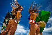 Photo of two girls in bikini on sandy dunes with haedphones tanning in the bright summer sun poster