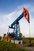 stock photo of nonrenewable  - Industrial oil pump jack in empty fileld - JPG