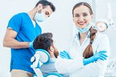 Portrait of a happy and confident female dentist wearing sterile white coat and surgical gloves, whi poster