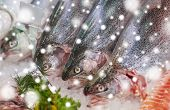 seafood, sale and food concept - chilled fresh fish on ice at grocery stall over snow poster