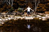 Young Man With Outstretched Arms Meditating Enjoying Nature On Peaceful, Calm Red Creek River In Dol poster