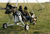picture of ultralight  - Two pilots of airborne motorized ultralight glider and green grass as a background - JPG