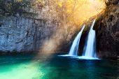 Sunbeams on amazing waterfall in Plitvice lakes. Plitvice National Park, Croatia. Landscape photogra poster