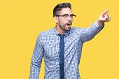 Young business man wearing glasses over isolated background Pointing with finger surprised ahead, op poster