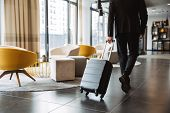 Cropped photo of caucasian businessman wearing formal black suit walking with suitcase in hotel lobb poster