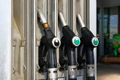 Gasoline And Petrol Products Concept. Black Fuel Pistols On Fuel Station. Pumping Petrol At Gasoline poster