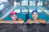 Front view of a young diverse woman and a Caucasian woman wearing swimming caps and goggles smiling  poster