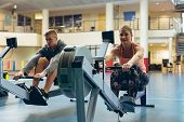 Front view of  young fit Caucasian male and female athlete exercising with rowing machine in fitness poster