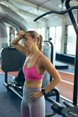 Side view of tired beautiful young Caucasian female athlete standing in fitness studio. Bright moder poster