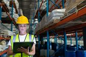 Front view of Caucasian Attentive female staff using digital tablet in warehouse. This is a freight  poster