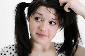 foto of dandruff  - confused young brunette woman touching her hair - JPG