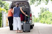Woman Holding Luggage With Driver Putting Luggage In Mini Bus Travel Concept. poster