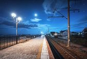 Beautiful Railway Station At Night In Summer. Starry Sky Over Railroad At Dusk. Industrial Landscape poster