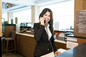 Happy Female Hotel Clerk Answering Phone While Making Eye Contact In Lobby At Hotel poster