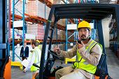 Side view of handsome mature Asian male worker talking on walkie-talkie while driving forklift in wa poster