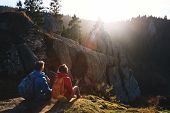 Couple Hikers With Backpacks Are Sitting On Edge Of Slope And Enjoying A Beautiful Morning Landscape poster