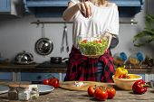 Young Cheerful Girl Prepares A Vegetarian Salad In The Kitchen, She Throws Pieces Of Cheese On A Pla poster