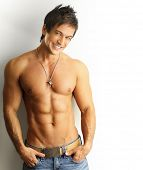 stock photo of six pack  - Sexy portrait of a young muscular male model with great happy smile against white wall - JPG