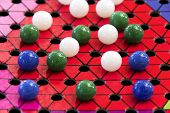 picture of chinese checkers  - A Chinese checkers board and different color marbles - JPG