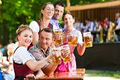 In Beer garden in Bavaria, Germany - friends in Tracht, Dirndl and Lederhosen and Dirndl standing in