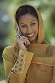 stock photo of dupatta  - Portrait of an Indian woman in traditional dress using cell phone - JPG