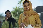 foto of dupatta  - Portrait of happy Indian woman holding shopping bags with female friend on a call in the background - JPG