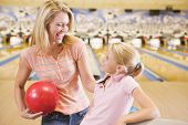 stock photo of bowling ball  - Man and son smiling at bowling alley - JPG