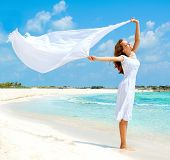 Beautiful Girl With White Scarf Jumping on The Beach. Travel and Vacation. Freedom Concept. Full len