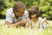 foto of father daughter  - Portrait of man and daughter lying in grass in summertime - JPG