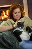 Teenage girl sitting at fireplace at home and fondling cat, affectionate smiling. poster