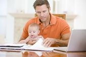 stock photo of x-files  - Man working from home with baby - JPG