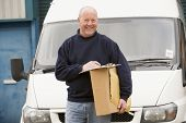 image of self-employment  - Delivery person standing by van with clipboard and package in hand - JPG