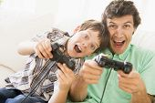 Man And Young Boy With Video Game Controllers Smiling poster