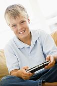Young Boy In Living Room With Handheld Video Game Smiling