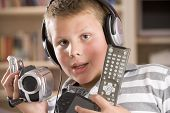 stock photo of gizmo  - Young boy using camcorder at home - JPG