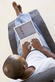 Man Sitting In Chair Using Laptop