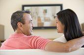 Постер, плакат: Пары в гостиной наблюдая телевидение улыбается