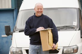 foto of self-employment  - Delivery person standing by van with clipboard and package in hand - JPG