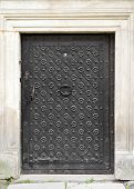stock photo of judas  - vintage gate with door knocker decorated with wrought iron - JPG
