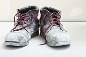 stock photo of boot  - pair of old dirty work boots in construction site - JPG
