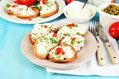 pic of hardtack  - Sandwiches with cottage cheese and greens on plate on wooden table close - JPG
