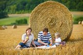 Happy Family Of Three Picnicking On Yellow Hay Field In Summer.