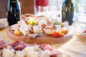 picture of brie cheese  - Cheese and fruits as appetizer with various types of cheese in background at dinner party - JPG