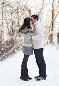 foto of mistletoe  - Happy young couple under mistletoe having fun in the winter park - JPG