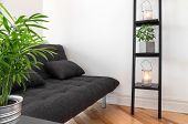 pic of futon  - Living room with gray sofa decorated with plants and lanterns - JPG